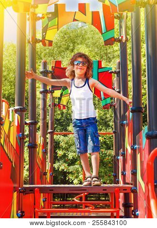 The Boy Is Having Fun On The Street Playground. Swings And Slides In The Park For Children. Children