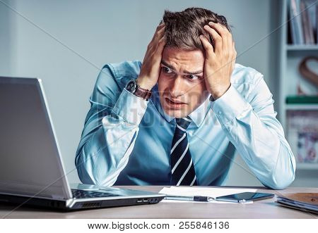 Shocked Businessman Dissatisfied His Earnings, Looking At Laptop. Photo Of Young Man Working In The