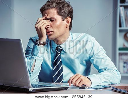 Young Office Man With Pain In His Head Or An Eye. Photo Of Man Suffering From Stress Or A Headache G