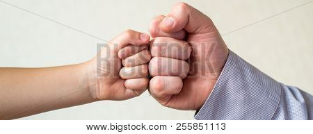 Competition And Victory, A Fist Of A Child And An Adult Male Close-up. Leader And Winner