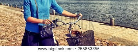 Bicycle commute in city street. Girl biking with bicycle walking on sidewalk in urban harbour old port. Woman in European city. Active healthy lifestyle. Banner panorama.