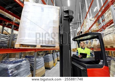logistic business, shipment and loading concept - loader with clipboard and cargo on forklift at warehouse