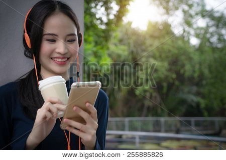 Woman Drinking Coffee Listening Music With Smartphone Headset. Happy Beautiful Girl Relax With Coffe