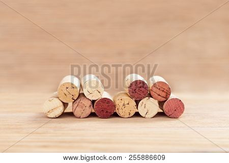 Old Used Corks From Wine Bottle On Blur Wooden Table With Copy Space. Natural Wood Fon With Corks Fr
