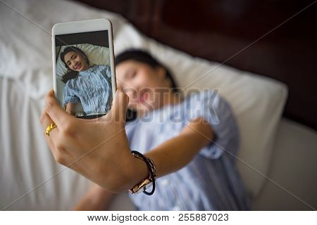 Young Happy Woman Taking  Selfie With Mobile Phone In Bedroom Morning. Asian Cute Girl Lying On Bed