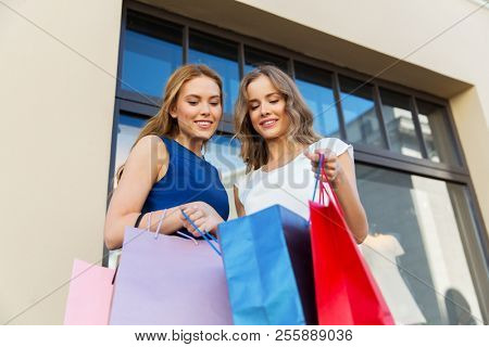 sale, consumerism and people concept - happy young women looking into shopping bags at storefront