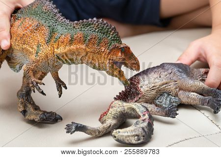 Kid Playing With Toys Of Acrocanthosaurus And Dinosaur Bloody Body On Sofa At Home