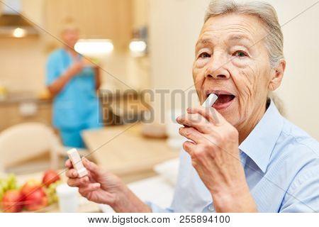 Senior woman creams her lips with lip cream in her senior citizen home