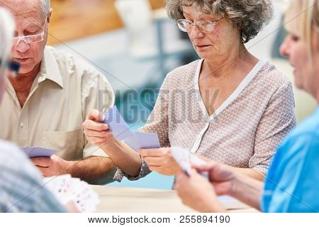 Group of seniors together playing cards at home or in a retirement home
