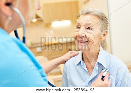 A doctor or nurse examines a senior woman with the stethoscope