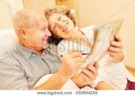 Happy seniors couple in senior residence resolves crossword puzzle