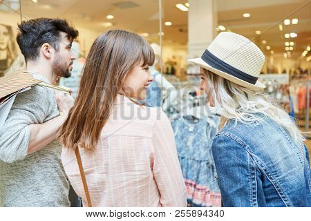 Teeanger as friends together while shopping in front of a fashion shop