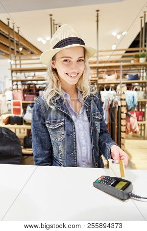 Young woman as customer holds credit card over the card reader at checkout