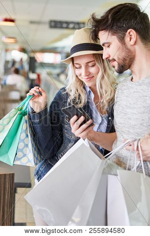 Young couple uses smartphone shopping app for retail price comparison
