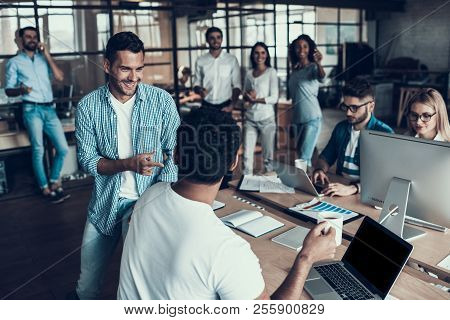 Young Smiling Business People At Work In Office. Group Of Young Coworkers Sitting Together At Table