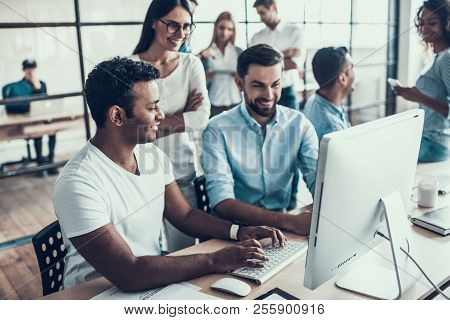 Young Smiling Business People Working In Office. Group Of Young Coworkers Sitting Together At Table