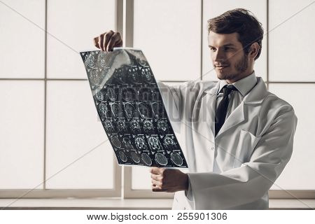 Young Smiling Doctor Looking At Mri Scan Of Brain. Handsome Young Man Wearing White Coat Examining M