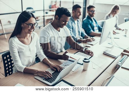 Young Smiling Business People Working In Office. Group Of Young Happy Collegues Sitting Together At