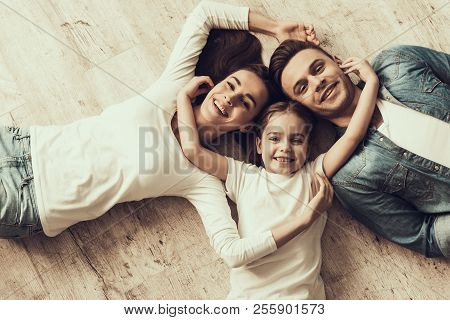 Happy Family Lying Of Floor Together At Home. Beautiful Woman Handsome Man And Adorable Little Girl