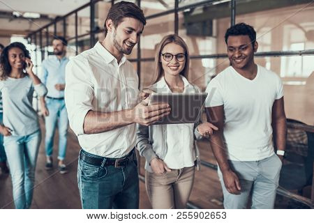 Group Of Young Business People Using Tablet. Young Smiling Man Showing Project On Tablet To Colleagu
