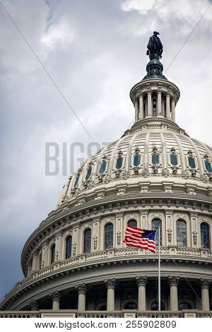 The United States Capitol Building In Washington Dc On A Cloudy Summer Day With Its Flag Waving In T