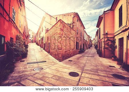 Vintage Stylized Picture Of A Street Corner In Alcudia Old Town At Sunset, Mallorca, Spain.