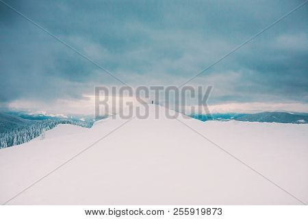 Silhouette Of A Man In The Distance In The Mountains. Winter Landscape. Snow-covered Mountains. A Lo