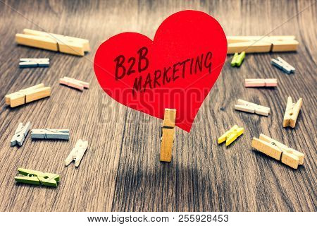 Word writing text B2B Marketing. Business concept for Partnership Companies Supply Chain Merger Leads Resell Clothespin holding red paper heart several clothespins wooden floor romance. poster