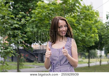 Waist-up Portrait Of Smiling Pretty Young Woman Showing Thumbs Up Standing On City Street. Cheerful