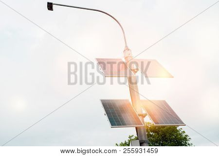 Street Lamp Poles Powered By Solar Energy. Solar Panels On Electric Pole For Lighting On The Road In
