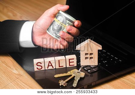 The Realtor's Hand Holds A Bundle Of Money At The House With The Keys. The Concept Of Buying And Sel