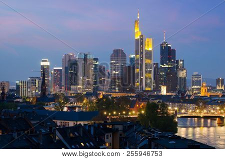 View Of Frankfurt Am Main Skyline At Dusk Along Main River With Cruise Ship In Frankfurt, Germany