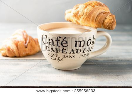 French Breakfast Is A Large Beige Cup Of Coffee With Milk And Croissants On A Wooden Table. On The C