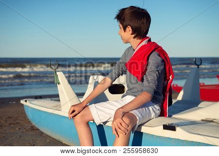 Young boy sitting on catamaran at the summer beach. Cute spectacled smiling happy 12 years old boy at seaside, looking at sea. Kid's outdoor portrait over seaside.