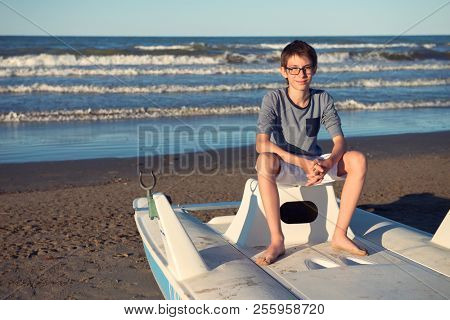 Young boy sitting on catamaran at the summer beach. Cute spectacled smiling happy 12 years old boy at seaside, looking at camera. Kid's outdoor portrait over seaside.