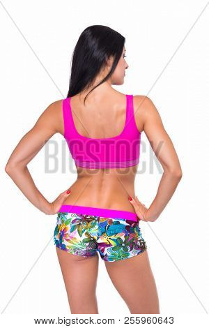 Portrait of slim fitness cheerful girl with perfect fit body thumb up in studio over white background, back view. Fitness, weight lose, fitness diet, workout programs for women concept.
