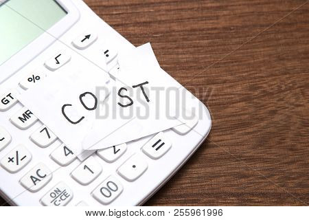 Cut The Word Cost Concept For Recession Or Credit Crisis And Calculator On Wood. Concept Of Cost Cut