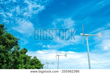 Horizontal Axis Wind Turbine With Blue Sky And White Clouds Near Green Tree. Wind Energy In Eco Wind
