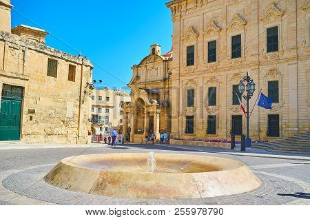 Valletta, Malta - June 17, 2018: The Modern Fountain In Castille Place With A View On St Catherine O
