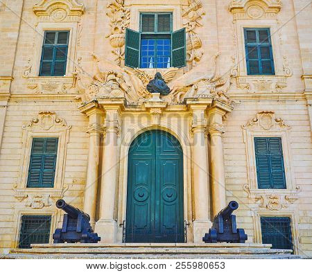 Main Entrance To Baroque Auberge De Castille Mansion With Big Wooden Door, Framed By Stone Columns,