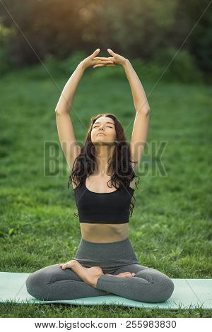 Young Girl Doing Yoga In The Park. Woman Practicing Yoga, Stretching In Lotus Position Outdoors With