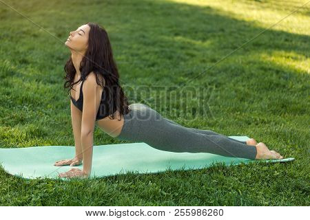 Woman Practicing Yoga Performing Yoga-asanas Outdoors. Young Attractive Slim Fitness Girl In Bodysui