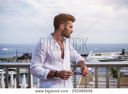 Attractive Fit Athletic Young Man Soaking In The Sun On Seaside Boardwalk Or Seafront, Wearing White