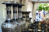 Black vases with gilded ornaments in a street shop. poster