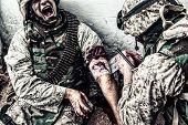 Military medic binding gunshot wound during fight poster