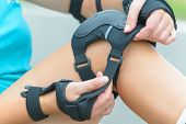 Woman rollerskater putting on knee protector pads on her leg and wearing wrist guards  poster