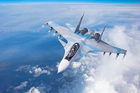 Combat Fighter Jet On A Military Mission With Weapons - Rockets, Bombs, Weapons On Wings Flies High