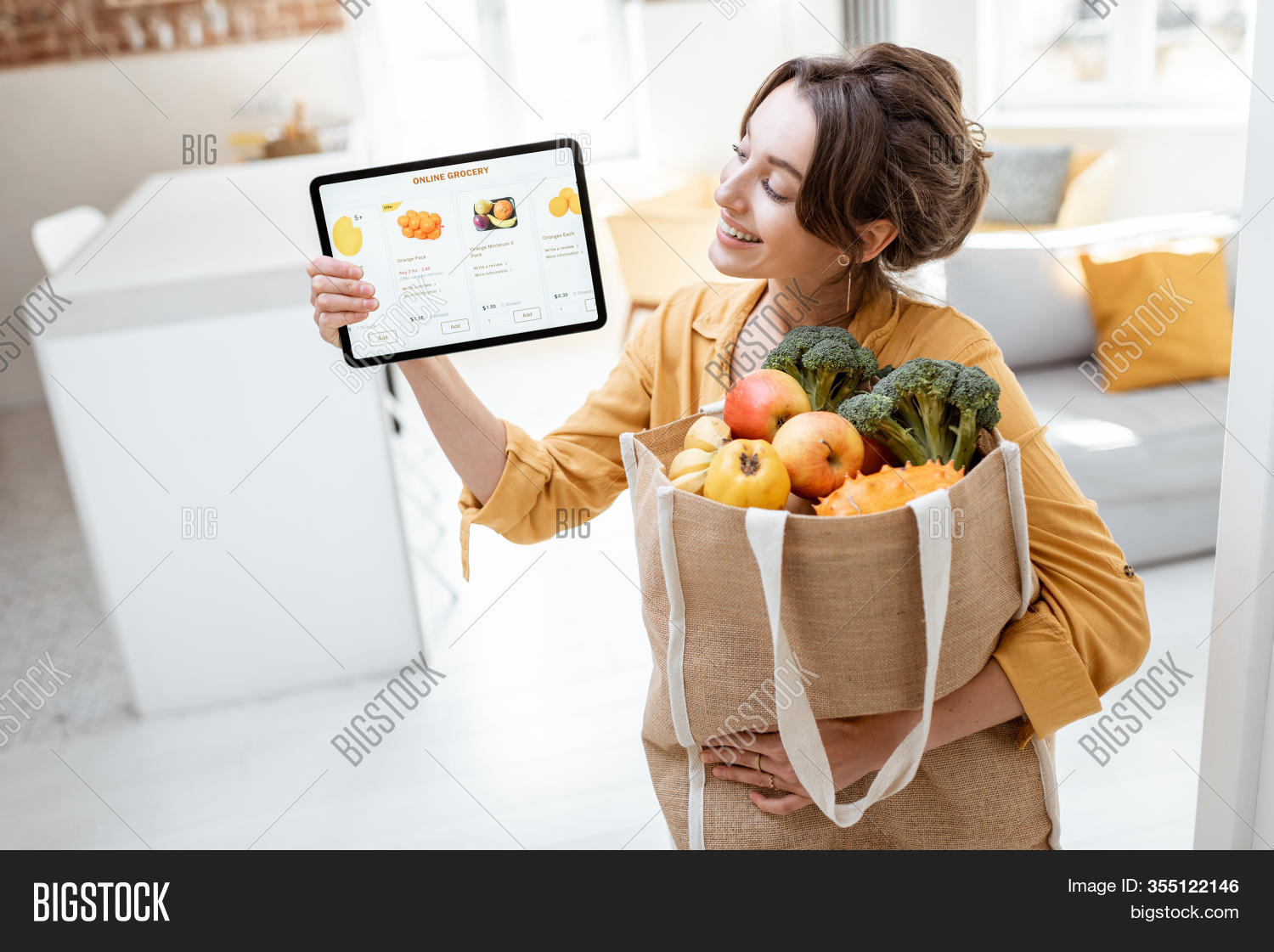 Happy Woman Holding A Digital Tablet With Launched Online Store While Standing With Shopping Bag Ful