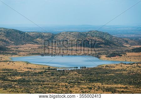 A Dam/lake At The Foot Of The Hills, Surrounded By The Dry And Bushy Plains Of Pilanesberg Nature Re