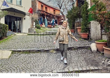 A Young Caucasian Female Tourist Descending Down A Street In The Turkish City Of Istanbul. A Pretty